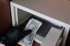 Thief in black gloves is stealing American dollars from the safe in the office. Wealth. Security. Stealing money from home or from. Stealing money from home or stock photos
