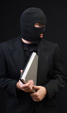 Stealing Office Equipment. A business thief wearing a black balaclava is stealing a laptop computer Royalty Free Stock Photography