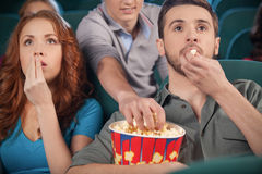Stealing popcorn. Young men stealing popcorn during the movie session in cinema Royalty Free Stock Images