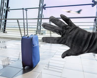 Stealing a suitcase. Closeup of a hand of a thief stealing a suitcase in the lobby of airport Stock Image