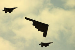 Stealth Bomber. American stealth bomber accompanied by two fighter planes Stock Images