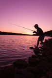 Stealthy Fisherman at Sunset. A fisherman silhouetted against a colorful sunset on a mountain lake Stock Image