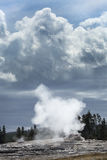 Steam and black clouds over Old Faithful geyser, Yellowstone, Wyoming. Stock Photography