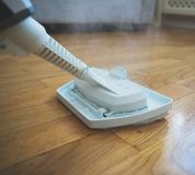 Steam cleaner. Cleaning the floor with a dry steam cleaner royalty free stock photos