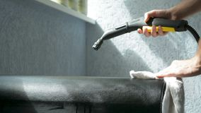 Steam cleaning a couch cushion with Karcher tool. Housecleaning concept. Closeup of a male hand holding a working steam cleaning device. Lots of water vapor stock footage