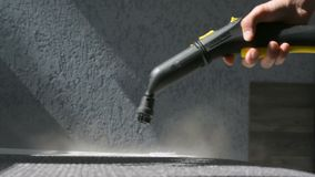 Steam cleaning a sofa with Karcher device. Home cleaning concept. Closeup of a male hand holding a working steam cleaning device. Lots of water vapor steam stock video