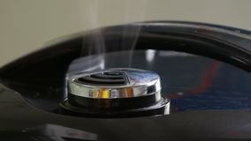 Steam comes out of the lid of black multicooker. Steam comes out of the lid of the black multicooker stock video