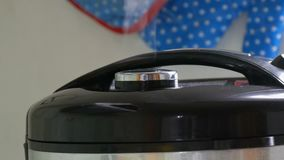Steam comes out of the lid of black multicooker. Steam comes out of the lid of the black multicooker stock footage