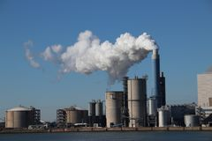 Steam coming out of the chimney at power plant in Rotterdam Maas. Vlakte in Netherlands stock photo