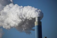Steam coming out of the chimney at power plant in Rotterdam Maas Royalty Free Stock Images