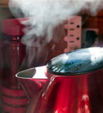 Steam coming out of red metal kettle. Sun light shining through kitchen window lighting the steam. A red metal kettle with black lid Stock Photo