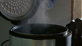 Steam in a cooking multicooker with an open lid in a kitchen. Steam in a cooking multicooker with an open lid in the kitchen stock footage