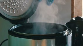 Steam in a cooking multicooker with an open lid in a kitchen. Steam in a cooking multicooker with an open lid in the kitchen stock video
