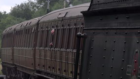 Steam engine with carriages comes into station 4K stock footage
