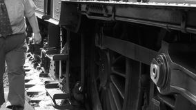 B&W shot of steam engine driver climbing from train 4K stock footage