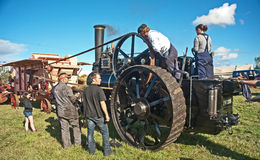 Steam engine driving threshing machine. Steam engine connected to threshing machine by belt; demonstration of early farming methods at Roseisle Rally on 22nd Royalty Free Stock Photo