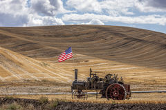 Steam engine and flag in field. The US flag on an old steam engine, in a wheat field at the Colfax Threshing Bee in Colfax, Washington royalty free stock photography