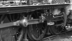 B&W steam engine low shot of wheels moving from stationary slowly forward 4K stock video