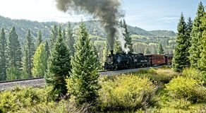 Steam Engine in the Rockies. Chama NM, USA, Sept. 19, 2017: A vintage steam locomoitve from the Cumbres & Toltec railroad clims toward Chama Pass in early autumn Stock Photos