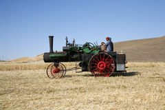Steam engine in a wheat field. An antique steam engine used to power the thresher that separates the wheat. Old time threshing bee in Colfax, Washington on royalty free stock photography