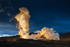 Steam erupting from geothermal power station at sunset royalty free stock images