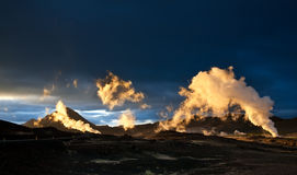 Steam erupting from geothermal power station at sunset Stock Images