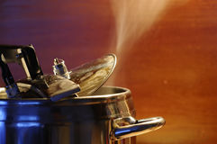 Steam escaping from lid of pressure cooker with reflection of modern kitchen. Indian style cooking rice or dhal stock images