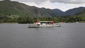 Steam ferry with holidaymakers and tourists Ullswater Lake District. Cumbria England UK with green hills stock footage