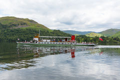 Steam ferry with holidaymakers and tourists Ullswater Lake District with green hills Stock Photography