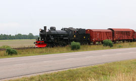 A steam freight train beside a road. Stock Images