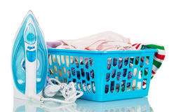 Steam iron and basket of linen for ironing on white. Royalty Free Stock Photos
