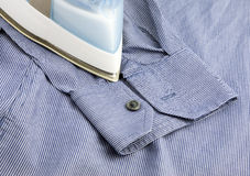 Steam iron on blue shirt Stock Photos