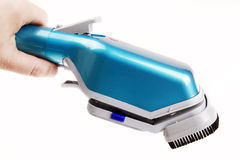 Steam iron brush. With a hand on white Stock Image