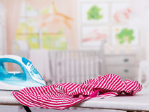 Steam iron and  clothes on  ironing board in  room. Stock Image