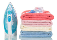 Steam iron and colorful towels isolated on white background. Stock Photo