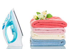Steam iron and colorful towels isolated on white Royalty Free Stock Image