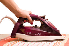 Steam iron in a female hand isolated on white background, ironing towels Royalty Free Stock Photography
