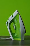 Steam iron. Green and white steam iron isolated on green background at home Royalty Free Stock Image
