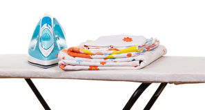 Steam iron, ironing board and bed linen isolated on white. Royalty Free Stock Image