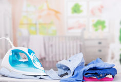 Steam iron, ironing board and clothes on  background of  room. Stock Photos