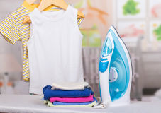 Steam iron, ironing board and clothes children in background room. Royalty Free Stock Photos