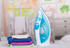 Steam iron and ironing clothes on  background of  room. Royalty Free Stock Photo