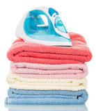 Steam iron and ironing colored towels isolated on white. Stock Photo