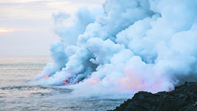 Steam from lava in seas Stock Images