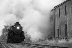 Steam locomotive. Arriving at station in rain past old warehouses Stock Photography