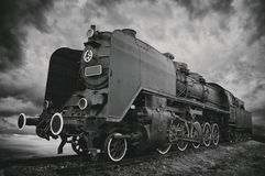 Steam locomotive. Old fashioned steam locomotive against dramatic sky. Dark black and white image royalty free stock photography