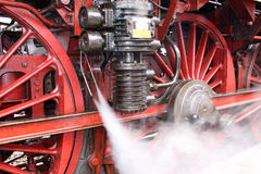 Steam Locomotive. Steam gushing out near the wheels, from the engine of an old locomotive stock image