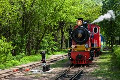 Steam locomotive going through the park Royalty Free Stock Images