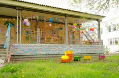 Steam locomotive made of plastic boxes and bottles on lawn next to terrace on playground.  stock image