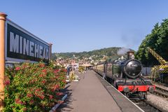 Steam locomotive 4160 at Minehead station, Somerset. On a cloudless sunny day, showing the station sign and decorative red fuchsia royalty free stock image